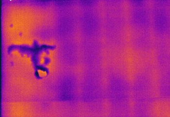 Thermogram shows cool spots caused by delaminated stucco on building facade. Thermogram taken from building exterior during early evening following a sunny day.